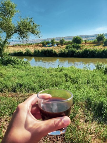שותה כוס קפה בבוקר על גדת הנהר